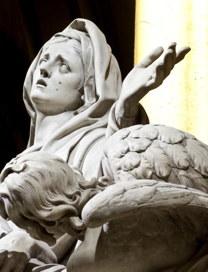 Statue en marbre blanc de la pieta mise en lumiere, une main tendue vers les cieux