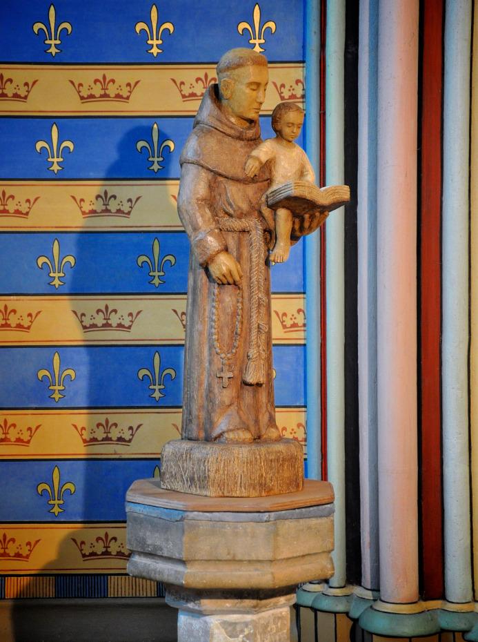 Statue de saint Antoine de Padoue lisant un livre à l'enfant dans ses bras à l'intérieur de la cathédrale Notre-Dame de Paris