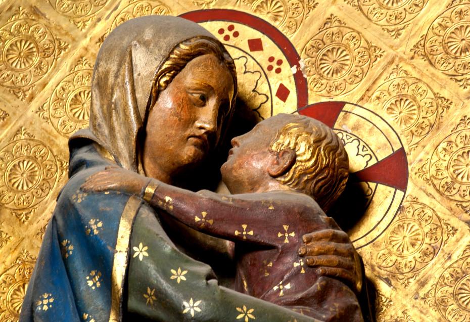Gros plan sur la Vierge portant l'enfant dans ses bras sur le tour de choeur, mur de gravures dorées