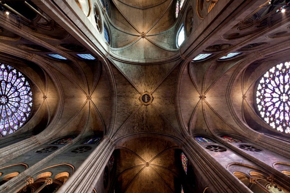 Photographie en contre-plongée de l'intérieur de la cathédrale, les plafonds symétriques avec des vitraux aux extrémitées
