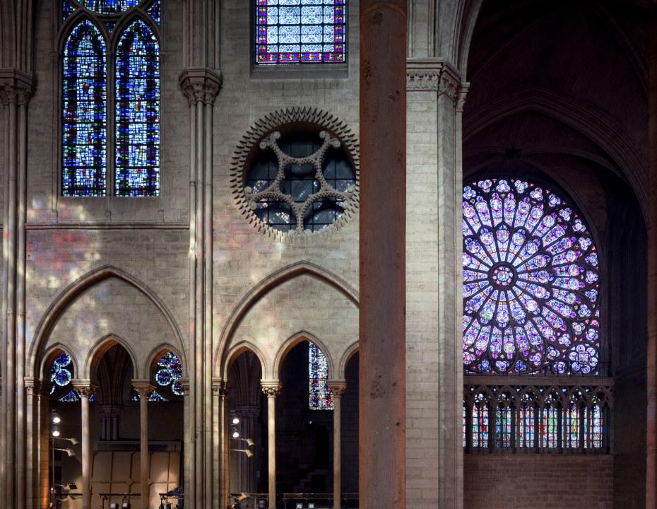 Dans Notre-Dame de Paris, vue d'ensemble des vitraux séparés par une colonne au premier plan de la photographie