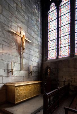 Un autel sculpté au dessus duquel se trouve deux chandeliers et un crucifix